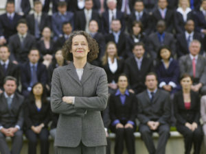 Business Woman Standing In Front Of Business People Sitting In Bleachers, Portrait